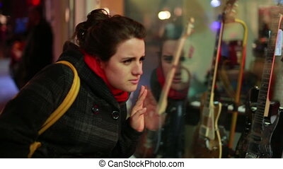 woman looks guitar shop window - Young woman looking to...