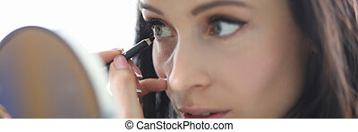 Woman looks in the mirror and paints her eyes