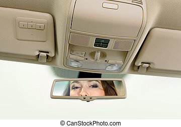 woman looks on the rear-view mirror