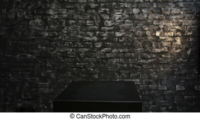 Woman looks out from behind a black box