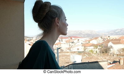 Woman looks out from the balcony and admire the city in the summer.
