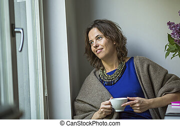 Woman looks out the window