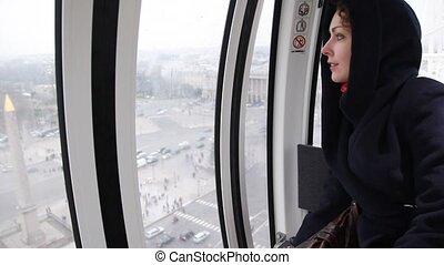 Woman looks Paris from above from Roue De Paris cabin -...