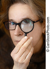 Woman looks through a magnifying glass.