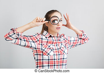 woman looks through a magnifying glass
