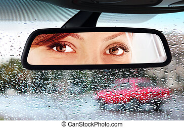 woman looks to rear-view mirror