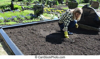 woman loosen grave ground - woman girl hands with rubber...