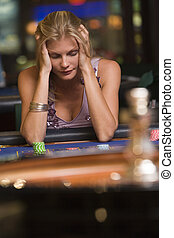 Woman losing at roulette table in casino