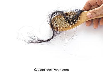 woman losing hair on hairbrush in hand