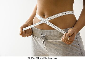 Woman losing weight - Woman standing pulling measuring tape...