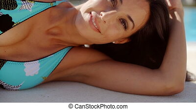 Woman Lying Down at the Poolside  Leaning on Arm