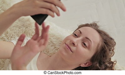 Woman lying down on the bed using her cellphone.