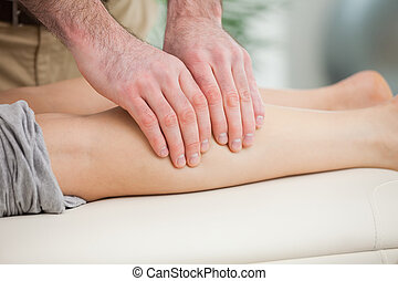 Woman lying forward while a man massaging her calf