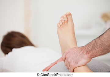 Woman lying forward while a physio manipulates her foot