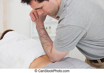 Woman lying forward while a physiotherapist is massaging her back in a physio room