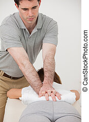 Woman lying forward while a physiotherapist massaging her back