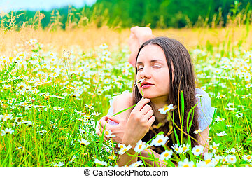 woman lying in a field and smelling a daisy