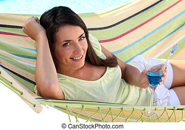 Woman lying in a hammock with a cocktail
