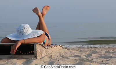 Woman lying in a lounger on the beach.