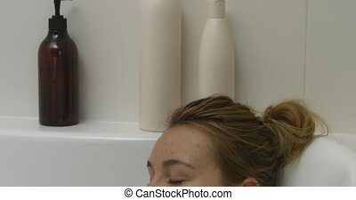 Woman lying in bathtub - Relaxed woman is lying in hot water...