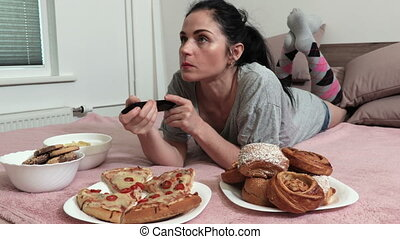 Woman lying in bed and eating sweet bun and piece of pizza