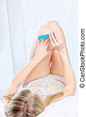 Woman lying in bed and polishing nails