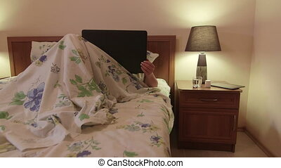 Woman lying in bed using laptop at night