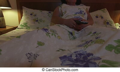 Woman lying in bed watching TV at night