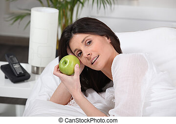 Woman lying in bed with an apple