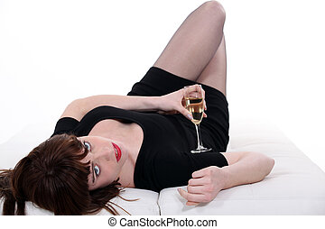 Woman lying in bed with champagne