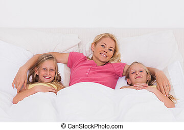 Woman lying in bed with her children