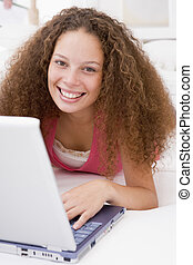 Woman lying in bed with laptop smiling