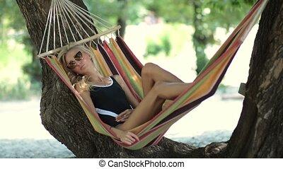Woman lying in hammock in tree's shadow on beach