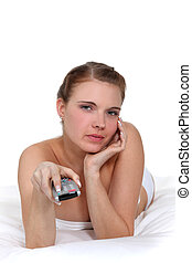woman lying in her bed and holding a remote control