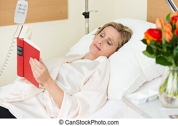 Woman lying in hospital reading a book