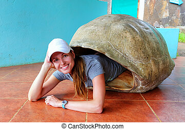 Woman lying inside empty Galapagos giant tortoise shell at the sanctuary on Santa Cruz Island, Galapagos National Park, Ecuador