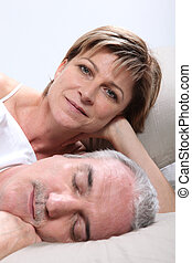 Woman lying next to her sleeping husband