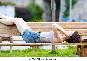 woman lying on a bench listening to music