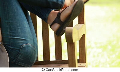 Woman lying on a bench wearing headphone