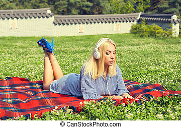 Woman lying on a green meadow and listening to music
