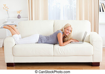 Woman lying on a sofa with a notebook in their living room