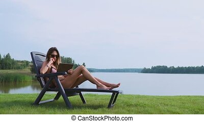 Woman lying on a sun lounger in a swimsuit with a tablet...