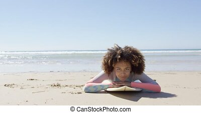 Woman lying on a surfboard - Smiling African woman lying on...