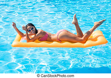 Woman lying on air mattress in the swimming pool - Portraito...
