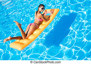 Woman lying on air mattress in the swimming pool - Portrait...