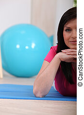 Woman lying on an exercise mat in a gym