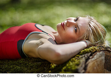 Woman lying on an old tree