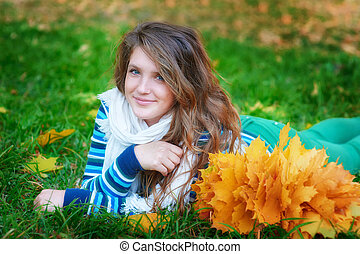 woman lying on autumn leaves outdoor portrait in park