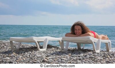 woman lying on beach bed in pebble beach, sea and clouds in background