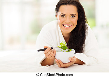 woman lying on bed eating vegetable salad